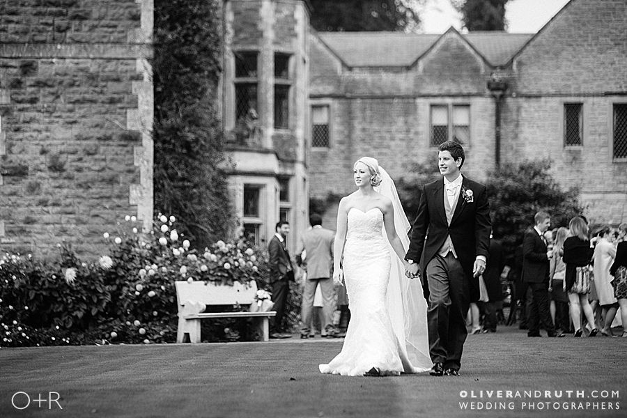 Bride and groom walking with Miskin Manor in background