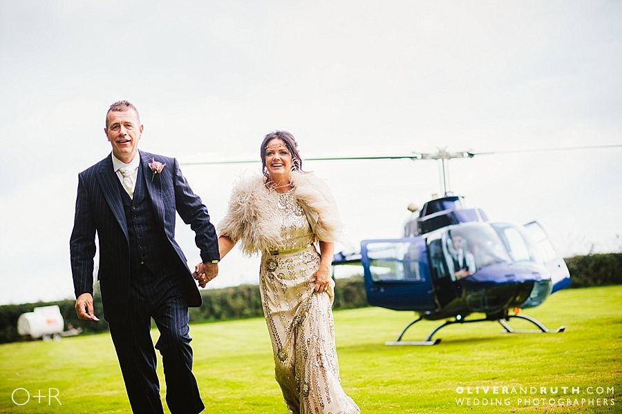 Wedding couple exit helicopter at Llansantffraed Court