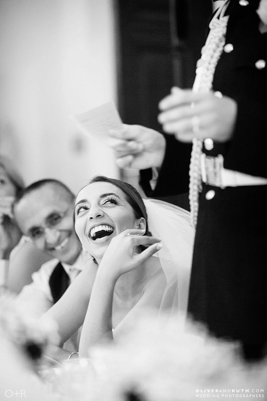 Bride laughing during groom's wedding speech at Llansantffraed Court