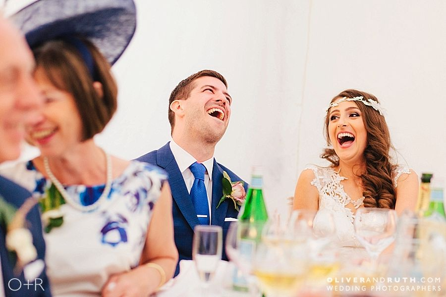 Bride and groom laughing during wedding speeches at Glangrwyney Court