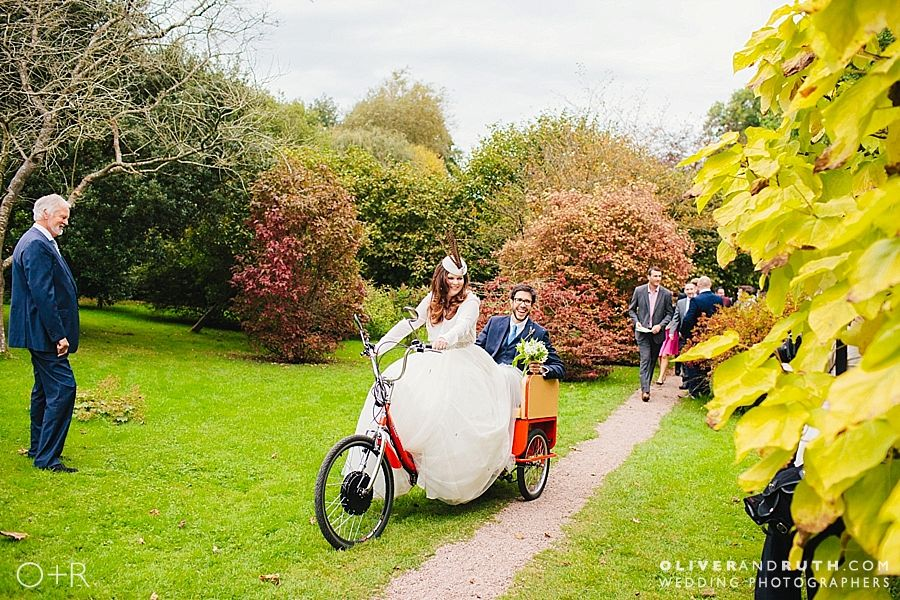 Bride and groom riding a tricycle at Dewsall Court