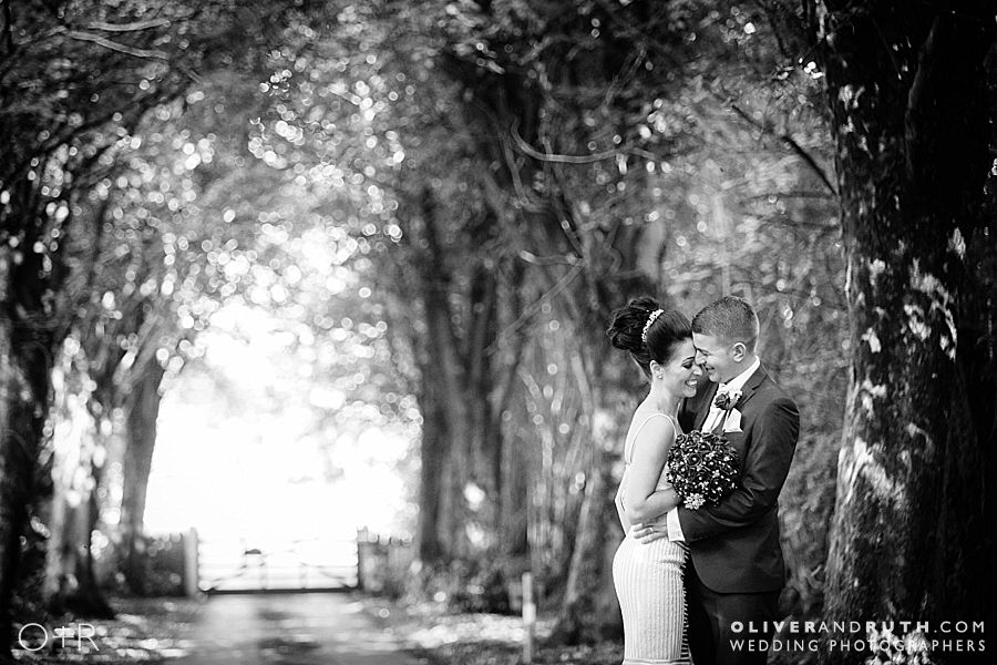 Bride and groom cuddling in the avenue of trees at Pencoed House