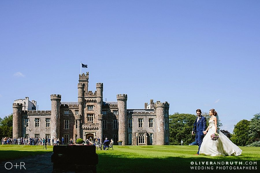 bride and groom walk in front of Hensol castle