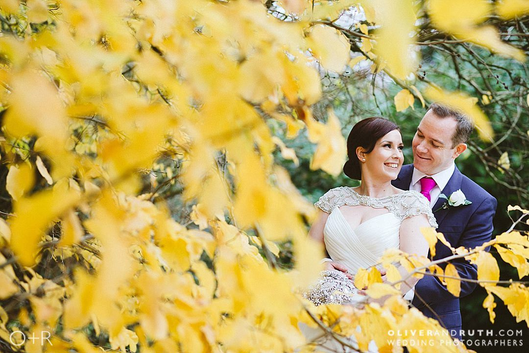 Bride and groom with yellow autumn leaves at Manor By The Lake, Gloucestershire