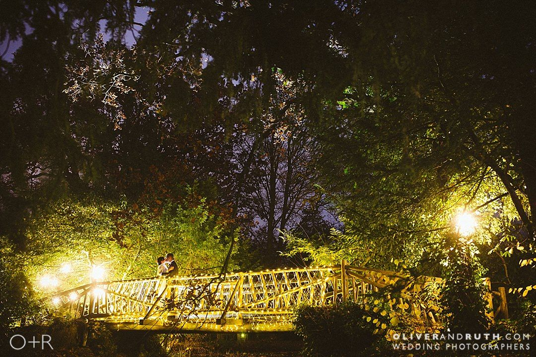 Bride and groom on the bridge with fairy lights at night at Manor By The Lake, Gloucestershire