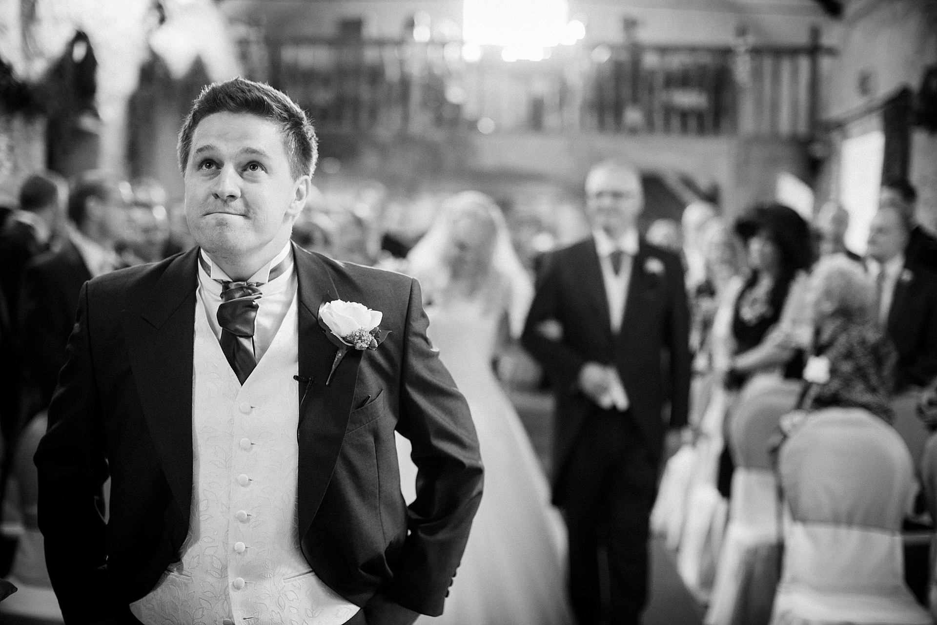 Groom looks emotional as his bride walks down the aisle