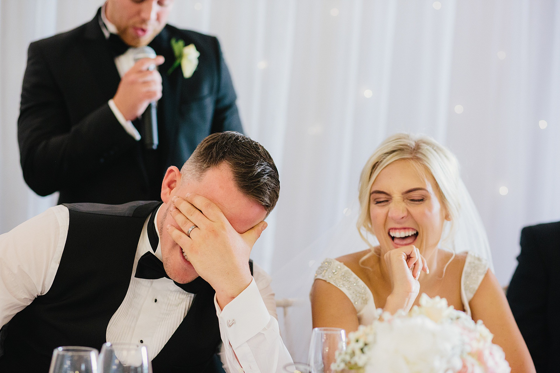 Bride and groom laughing at the best man's wedding speech