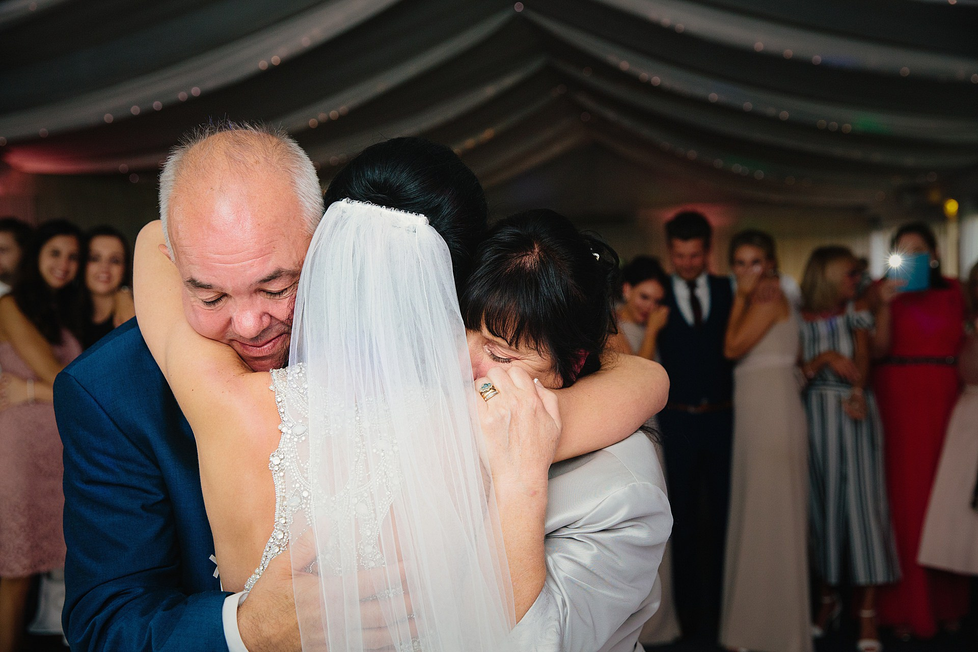 Bride get's a hug from her parents